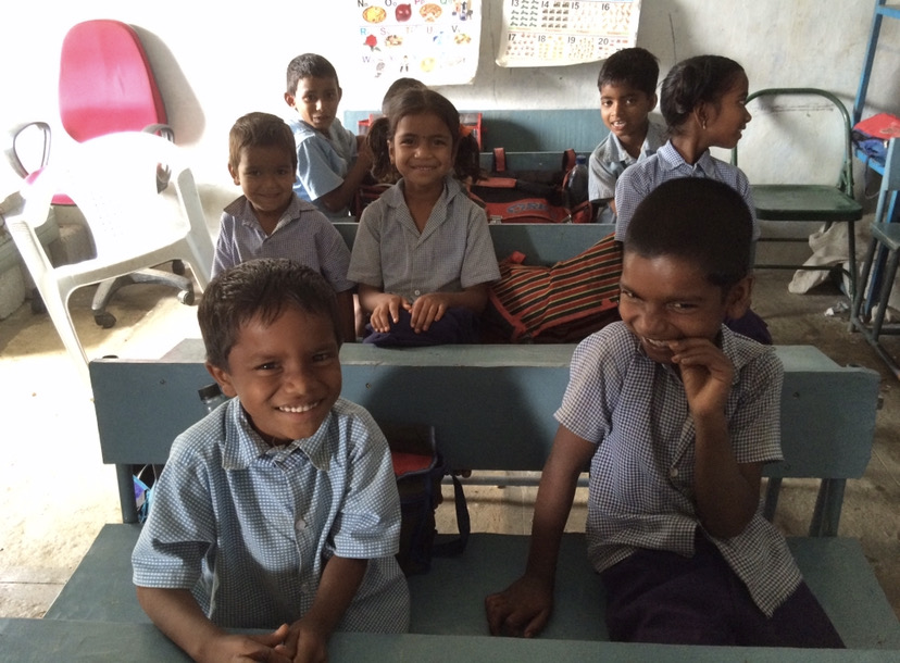 Eight school children in uniform in a classroom in India. This icon is being used to depict voice and participation which is one of the research themes that CaNDER members are involved in.