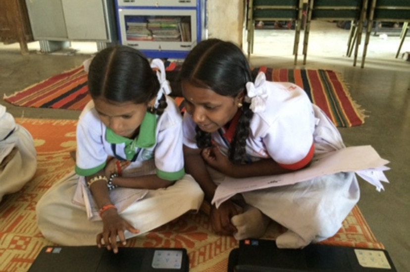 This image depicts two school girls studying using a computer in their classroom. They are seated on the floor on mats and learning together. This icon is being used to depict counting for accountability which is one of the research themes that CaNDER members are involved in.