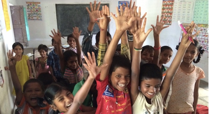School students in India smiling and hands raised in celebration of the end of a teaching and learning session.